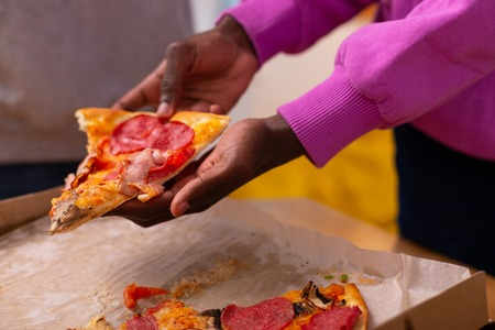 Pizza with salami. Dark-skinned teenager in purple sweatshirt holding pizza with salami