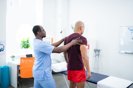 Sports therapist. Dark-skinned sports therapist standing near his visitor wearing red shorts and dark red t-shirt