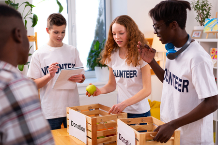 Food for donation. Teenagers putting food for donation into boxes working in voluntary company together Imagens