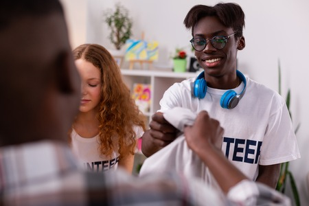 Clothes for donation. Dark-skinned teenager in glasses gathering clothes for donation with friends Stock Photo