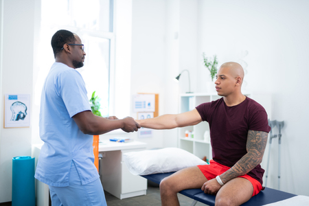 With nice biceps. Young tattooed sportsman with nice biceps visiting therapist after getting injury