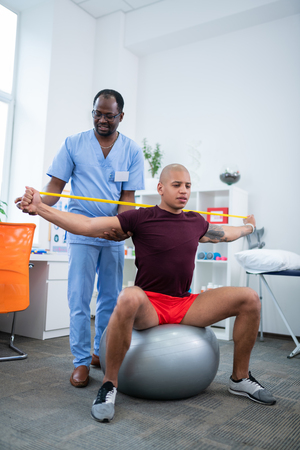 Standing near man. Physical therapist in uniform and glasses standing near man sitting on fitness ball