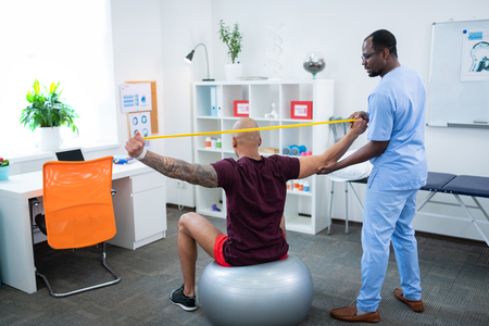 Stretching for back. Bald man with big tattoo on arm doing stretching for back visiting physical therapist