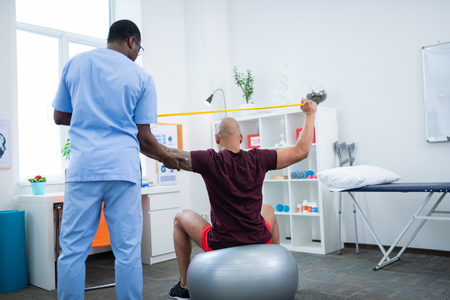 Therapist holding hand. African-American therapist holding hand of man doing stretching after injury 写真素材