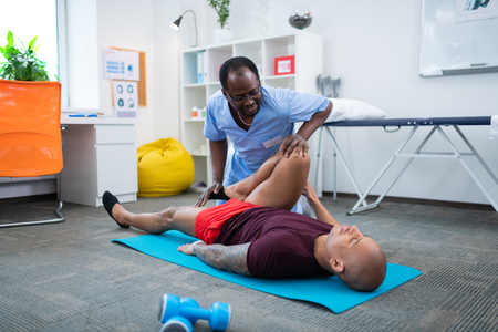 Knee injury. Sportsman with knee injury visiting physical therapist wearing blue uniform