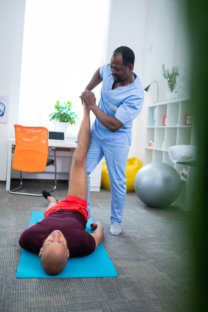 Having therapy. Sportsman in red shorts lying on sport mat and having physical therapy