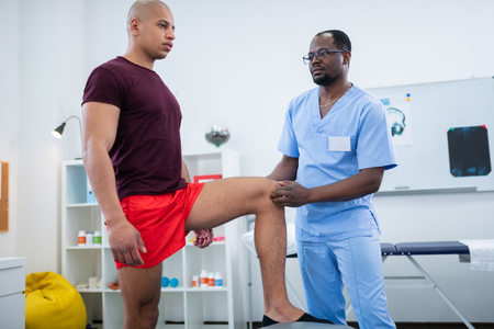 Knee after injury. Therapist in glasses and blue uniform examining knee of sportsman after injury 写真素材