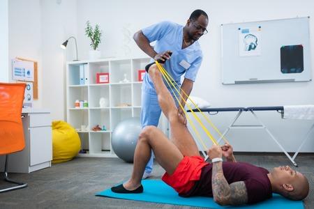 Near professional therapist. Tattooed strong bodybuilder stretching legs near professional therapist 版權商用圖片