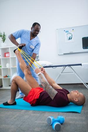 Rehabilitation time. Man wearing smart watch stretching legs after injury having rehabilitation near therapist 写真素材