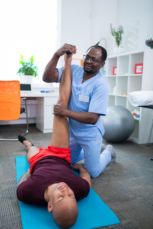 Stretching legs. Dark-skinned therapist in glasses stretching legs for sportsman with injury 版權商用圖片