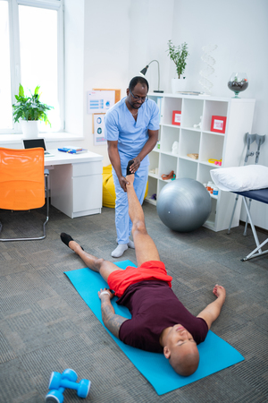 With leg injury. Dark-skinned therapist in uniform standing near patient with leg injury lying on mat