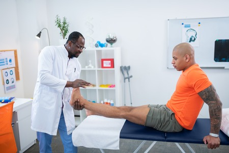 Therapist after training. Tattooed sportsman wearing smart watch visiting therapist after training
