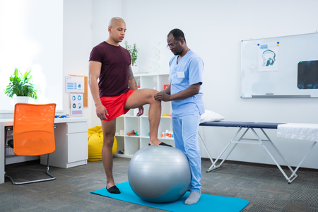 Touching knee. Physical therapist in blue uniform touching knee of sportsman standing near fit ball
