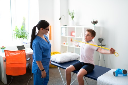 Showing needed exercises. Smiling positive long-haired woman explaining sportive procedure while working with younger client