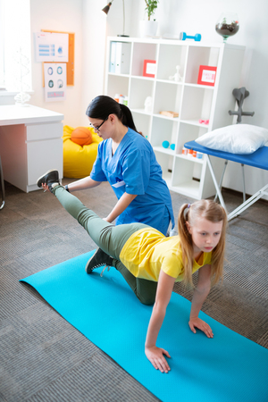 Leaning on mat. Careful dark-haired physical therapist holding leg of training girl while staying in personal cabinet