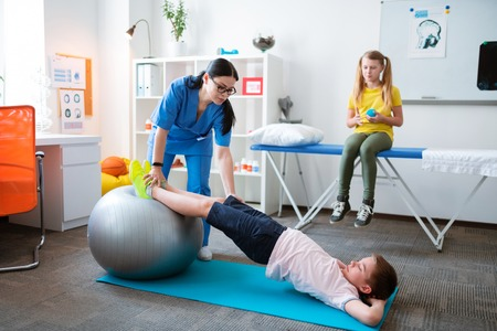 Explaining important details. Active little patient stretching whole body while leaning on pilates ball with assistance of specialist