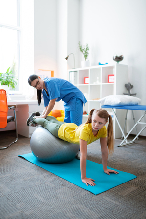 Visiting professional physiotherapist. Accurate hard-working girl leaning on grey Pilates ball and training balance and functioning