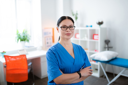 Concentrated long-haired therapist. Proud Asian dark-haired physical therapist wearing professional blue uniform while staying in personal cabinet