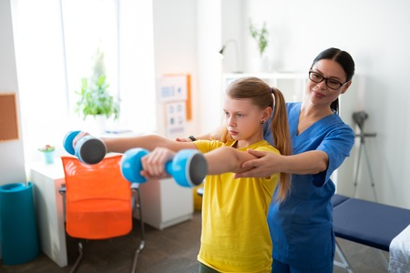 Raising dumbbells. Supportive positive dark-haired nurse touching little girl during appointment and examining functions of body Standard-Bild