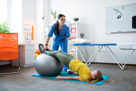 Training musculoskeletal system . Professional dark-haired therapist helping little girl with stretching important body muscles Фото со стока