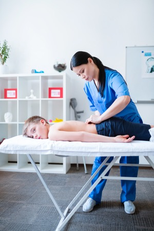 Experienced Asian master. Accurate skilled woman in blue uniform massaging back of relaxed little patient