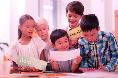 Teamwerk. Groep actieve schoolkinderen die nieuwe Engelse woorden leren en ze op vellen papier houden. Stockfoto