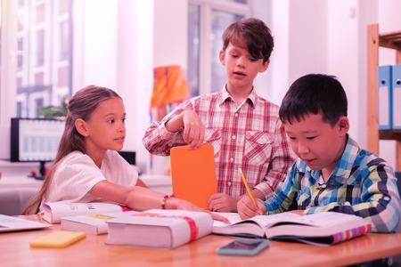 Hablar de la tarea. Tres niños inteligentes, dos niños y una niña haciendo su trabajo de clase juntos usando libros y una tableta. Foto de archivo