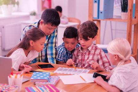 Einrichten eines Zeitplans. Gruppe konzentrierter Schulkinder, die gemeinsam ihren neuen Stundenplan erkunden. Standard-Bild