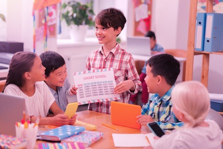 Public speaking. Smiling boy standing in front of his laughing friends with school timetable in his hands.