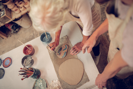 Feeling inspired. Top view of a nice aged woman holding a brush while painting Stock fotó