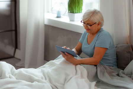 Watching movie. Nice-appealing cheerful happy charming white-haired serene old lady wearing a blue t-shirt watching a movie on a tablet while lying in the bed