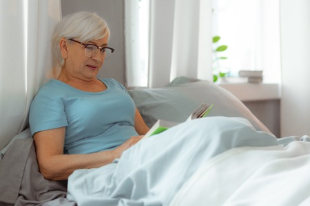 Elderly woman reading. Charming good-looking white-haired elderly lady in eyeglasses lying in the bed and reading a book.