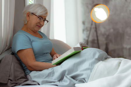 Reading a book in the bed. Charming nice-looking grey-haired aged lady wearing eyeglasses lying in the bed and engaging in a book reading.