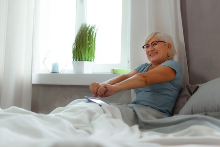 Stretching after sleeping. Active energetic appealing silver-haired charming nice-appealing elderly female wearing eyeglasses and blue t-shirt and stretching her arms after sleeping
