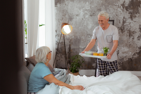 Breakfast on a tray. Attractive handsome aged white-hair spouse wearing pajama serving breakfast on a tray to the bed of his aging beautiful nice-appealing wife.