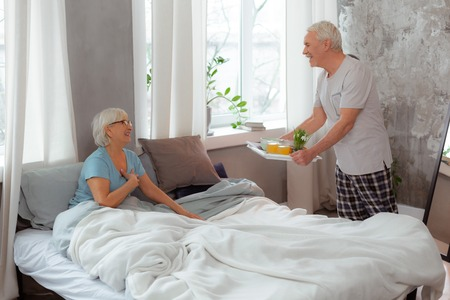 Bringing breakfast on the tray. Cheerful handsome aged loving husband wearing pajama bringing breakfast on the tray to the bed of his beaming glowing nice-appealing elderly wife.