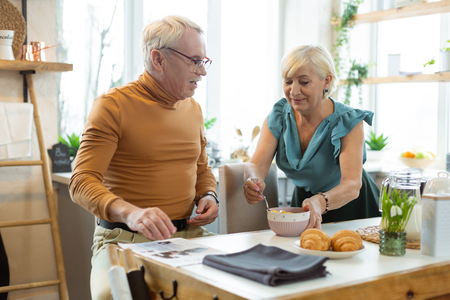Giving a breakfast. Caring charming loving grey-haired wife wearing stylish top giving a breakfast to her attractive nice-looking stylish aging spouse 写真素材
