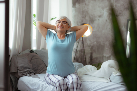 Stretching in the bed. Vigorous beaming energetic delightful nice-looking aged female with short grey hair wearing eyeglasses and nightclothes doing stretching after the good sleep in the bed