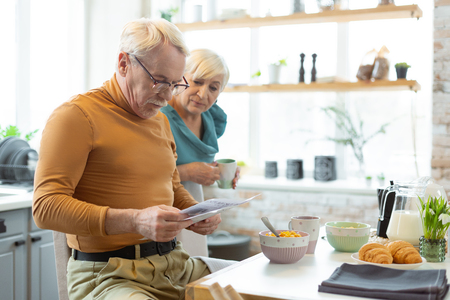 Reading a newspaper. Focused stylish attractive grey-haired bearded man wearing mustard sweater and eyeglasses reading newspaper while his aging charming appealing wife looking at him