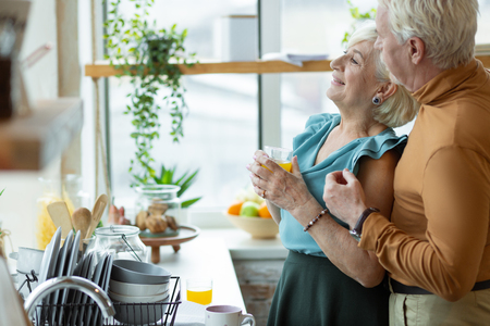 Husband and wife. Portrait of smiling attractive vigorous handsome silver-haired male with beard lovingly cuddling his appealing charming delightful aged wife at the kitchen.