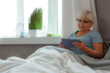 Holding a tablet. Glowing cheerful alluring charming grey-haired serene woman in blue t-shirt watching movie on a tablet while spending time in the bed.