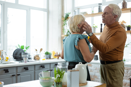 Touching the face. Loving caring handsome attractive kind white-haired bearded man tenderly touching the face of charming elegant silver-haired appealing wife.