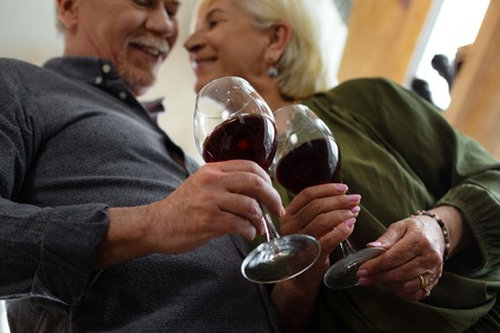Glasses of wine. Close-up picture of attractive elderly white-haired happy married couple in love holding glasses of wine in hands standing at the kitchen 免版税图像