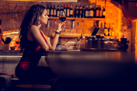 Woman holding glass. Slim stylish woman wearing bracelet holding glass of wine while waiting for boyfriend