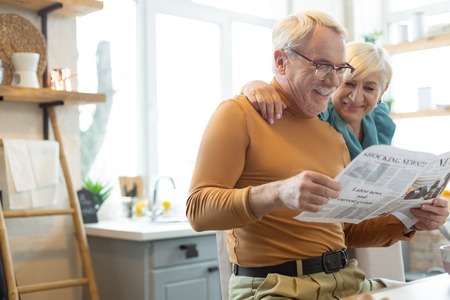 Embracing a spouse. Smiling attractive glowing handsome silver-haired bearded man in a mustard sweater engaging in reading a paper while his tender aging white-haired spouse embracing him.