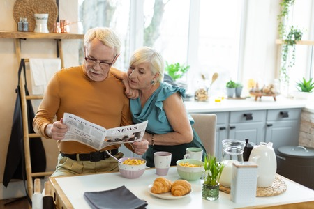 Reading during a breakfast. Focused appealing happy contended well-dressed aging silver-haired spouses reading a newspaper together while sitting at the kitchen table. Banco de Imagens