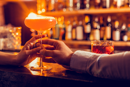 Man bringing cocktail. Close of man bringing nice cocktail for his girlfriend while having date