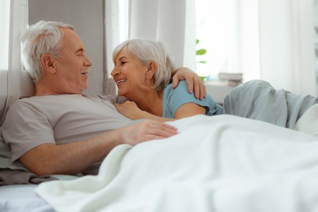 Lovingly embrace wife. Beaming nice-looking attractive silver-haired bearded man in the ivory t-shirt lovingly embracing his smiling aged cheerful short-haired spouse