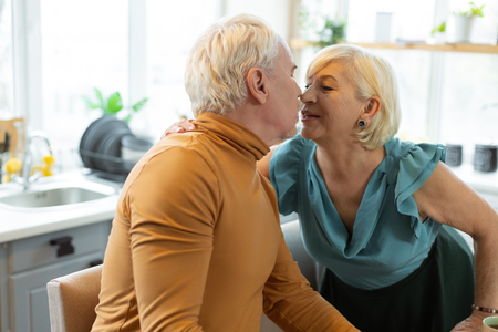 Kissing elderly couple. Happy elegant alluring aging spouse with short white hair wearing stylish clothing tenderly kissing her aged grey-haired husband. Stock Photo