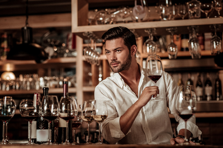 Cheerful brunette male leaning elbow on table while going to taste red wine